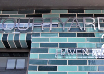 Laser cut stainless steel letters mounted to an acrylic panel